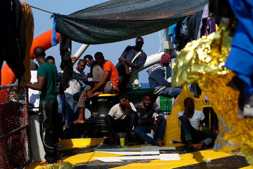 Migrants sit at the stern of the Medecins san Frontiere (MSF) rescue ship Bourbon Argos somewhere between Libya and Sicily August 8, 2015.  Some 241 mostly West African migrants on the ship are expected to arrive on the Italian island of Sicily on Sunday morning, according to MSF.<br /> REUTERS/Darrin Zammit Lupi <br /> MALTA OUT. NO COMMERCIAL OR EDITORIAL SALES IN MALTA