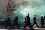 Metropolitan police in riot gear marching to change positions amidst smoke from flares between protesters of the Free Tommy Robinson demonstration, and their opposition organised by anti-fascist groups including Stand up to Racism who are opposed to far right politics on 24th August 2019 in London, United Kingdom. Some 250 Stand Up To Racism and other anti-fascist groups took to the streets today in opposition to supporters of jailed 'Tommy Robinson' real name Stephen Yaxley-Lennon at Oxford Circus, who gathered outside the BBC.