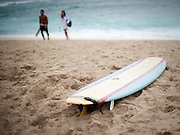 A single surfboard waits on Sunset Beach along the North Shore of Oahu, Hawaii