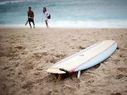 A single surfboard waits on Sunset Beach along the North Shore of Oahu, Hawaii