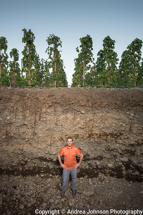 Christophe inside pit dug next to vines to showing depth of vine roots and rocks, Cayuse's Tribe vineyard