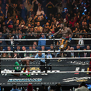 Deontay Wilder (R) waits in the neutral corner as Luis Ortiz falls to the mat during the WBC Heavyweight Championship boxing match at Barclays Center on Saturday, March 3, 2018 in Brooklyn, New York. Wilder would win the bout by knockout in the tenth round to retain the title and move to 40-0. (Alex Menendez via AP)
