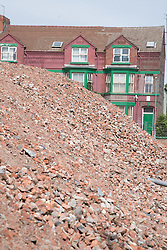 Pile of rubble from demolished houses in the foreground of a row of occupied houses in the area scheduled for the pathfinder regeneration scheme Bootle; Liverpool; England,