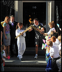 The Prime Minister David Cameron and his wife Samantha look on as (left) Kate Nesbitt MC hands over the Olympic flame to Florence Rowe (right) in Downing St, as she heads of to the next leg of the Olympic torch relay on the eve of the Olympic games, Thursday July 26, 2012. Photo by Andrew Parsons/i-Images.All Rights Reserved ©Andrew Parsons.See Instructions