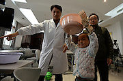 WUHAN, CHINA - NOVEMBER 16: (CHINA OUT) <br /> <br /> 3D-Printed Hand Completed<br /> <br /> A child wears 3D-printed hand while carrying a  plastic basin at Wuhan Third Hospital on November 16, 2015 in Wuhan, Hubei Province of China. A child, a farmer Liu Tao\'s son, fell into a fiery pit where straws was burning when he was only three years old. Left ear and left hand got injured heavily that the left hand had to be cut. While a phone in May this year from Wuhan Third Hospital gave them hope that the lost left hand could be replaced by 3D-printed hand and luckily it made success on the child finally.<br /> ©Exclusivepix Media