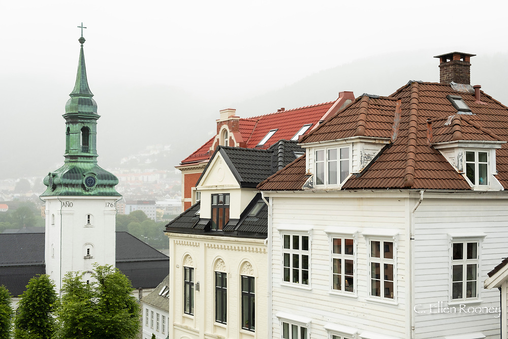 A church and old houses on a foggy day in the Nordness section of Bergen, Vestlandet, Norway