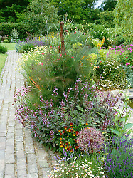 Rusty obelisk surrounded with bronze fennel, purple sage, Allium christophii and mexican daisies with brick path leading into the distance.