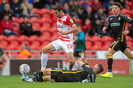Doncaster Rovers midfielder Matty Blair jumps Bradford city midfielder James O'Brien during the EFL Sky Bet League 1 match between Doncaster Rovers and Bradford City at the Keepmoat Stadium, Doncaster, England on 22 September 2018.