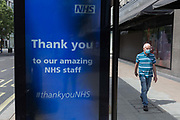 During the UKs Coronavirus pandemic lockdown and in the 24hrs when a further 255 deaths occurred, bringing the official covid deaths to 37,048, <br /> a pedestrian walks past a digital ad thanking NHS staff National Health Service at a bus stop on Oxford Street, on 26th May 2020, in London, England.