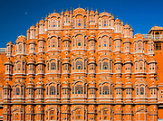 "Hawa Mahal (""Palace of Winds"" or ""Palace of the Breeze""), is a palace in Jaipur, India. It was built in 1798 by Maharaja Sawai Pratap Singh, and designed by Lal Chand Ustad in the form of the crown of Krishna, the Hindu god. Its unique five-storey exterior is also akin to the honeycomb of the beehive with its 953 small windows called jharokhas that are decorated with intricate latticework. The original intention of the lattice was to allow royal ladies to observe everyday life in the street below without being seen, since they had to observe strict ""purdah"" (face cover). Besides this, the lattice also provides cool air caused by the Venturi effect (doctor breeze) through the intricate pattern and thereby air conditioning the whole area during the high temperatures in summers. Built of red and pink sandstone, the palace is situated on the main thoroughfare in the heart of Jaipur's business centre. It forms part of the City Palace, and extends to the Zenana or women's chambers, the chambers of the harem. It is particularly striking when viewed early in the morning, lit with the golden light of sunrise."