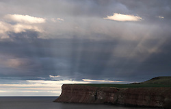 © Licensed to London News Pictures. <br /> 23/03/2015. <br /> <br /> Saltburn, United Kingdom<br /> <br /> Anticrepuscular rays are seen over Huntcliff in Saltburn.<br /> <br /> They are quite rare and appear to emanate not from the sun, but from the point on the horizon directly opposite it.You can only see them when you stand with the sun directly behind you.The shadows of individual clouds behind you are cast onto the cloud layer in front causing the effect.<br /> <br /> Photo credit : Ian Forsyth/LNP