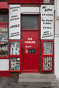 A doorway of a holiday trinket shop featuring ear piercing, joke items in the other holiday seafront memento shop on Pier Hill at Southend-on-Sea, Essex. Southend-on-Sea is a seaside town on the north side of the Thames estuary 40 miles 64 km east of central London. In its heyday, the working class visited from the capital when train transport allowed them to enjoy its beaches and the worlds longest pier. Its splendour faded on the advent of package holidays to Spain etc.