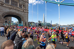 © Licensed to London News Pictures. 03/10/2021. London, UK. Runners run Tower Bridge during the London Marathon 2021. Photo credit: Ray Tang/LNP