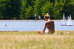 A woman enjoys the sunshine in Kensington Gardens as another heatwave day begins with temperatures expected to soar. London, July 01 2018.