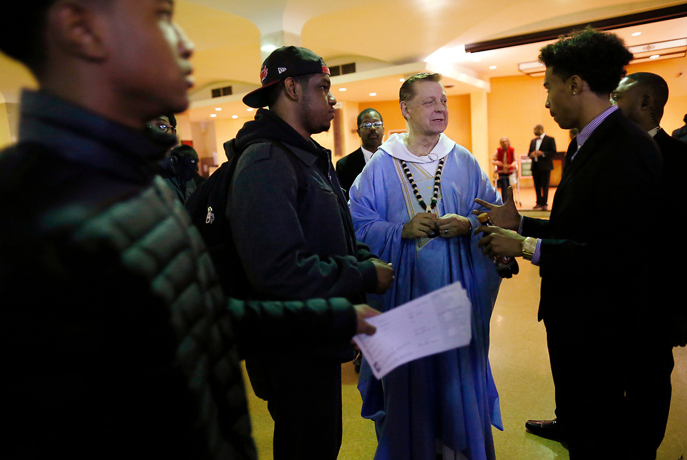 Father Michael Pfleger (2nd R) speaks to Justin Irving (R) and Kristopher Williams (2nd L) after a Sunday Service at Saint Sabina Church in Chicago, Illinois, U.S., December 4, 2016.   REUTERS/Jim Young