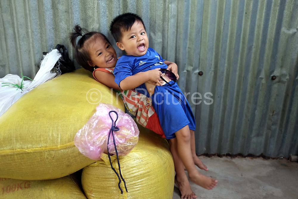 Two of Kum Van Nguyen and Giao Kim Ly's four grandchildren playing at home in Number 18 village, Nguyen Phich commune in the southern province of Ca Mau in Vietnam's Mekong Delta. Kum Van Nguyen and Giao Kim Ly live with two of their five children and four grandchildren.