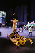 A man and his child play inside an inflated giraff toy in Wuxi, Jiangsu Province, China on 26 September 2012. Confronted with an aging population, the Chinese government is now considering phasing out the one child policy.