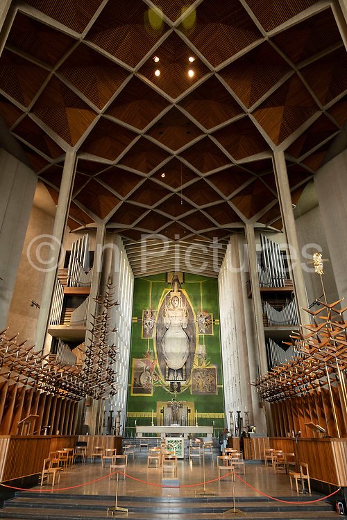 Christ in Glory in the Tetramorph, tapestry by Graham Sutherland<br /> inside Coventry Cathedral also known as St Michaels, a modern cathedral founded in 1956 and well known for having stunning modernist stained glass, minimalist structure and large scale tapestry on 23rd June 2021 in Coventry, United Kingdom. The Cathedral Church of Saint Michael, commonly known as Coventry Cathedral, is the seat of the Bishop of Coventry and the Diocese of Coventry within the Church of England. The current St Michaels Cathedral, built next to the remains of the old, was designed by Basil Spence and Arup, built by John Laing and is a Grade I listed building.