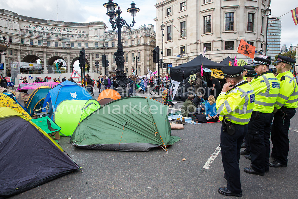 London, UK. 9 October, 2019. Police officers observe tents pitched by climate activists from Extinction Rebellion blocking Trafalgar Square on the third day of International Rebellion protests to demand a government declaration of a climate and ecological emergency, a commitment to halting biodiversity loss and net zero carbon emissions by 2025 and for the government to create and be led by the decisions of a Citizens' Assembly on climate and ecological justice.