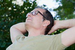 Mature man thinking and relaxing in garden