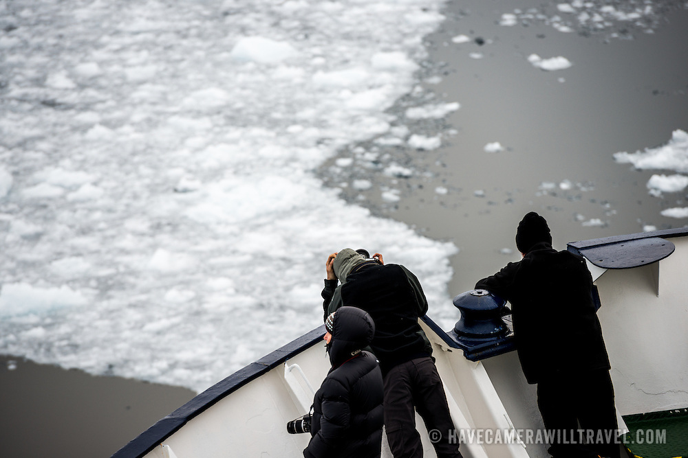 """Passengers stand on the bow of an ice-strengthened Antarctic cruise ship as it navigates the narrow Lemaire Channel on the western side of the Antarctic Peninsula. The Lemaire Channel is sometimes referred to as """"Kodak Gap"""" in a nod to its famously scenic views."""