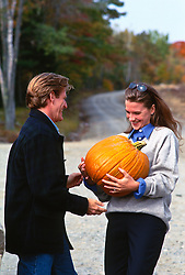 woman holding a very large pumpkin while a man attempts to help her