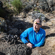 A hiker climbing Mt Kilimanjaro takes a detour to explore an underground cave through a small opening.