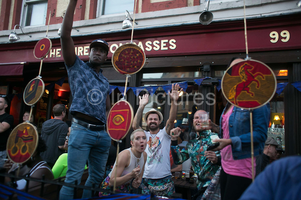 Crowds gathered outside the Three Compasses pub cheering the last carnival floats of the day in Dalston Lane  in East London, United Kingdom,Sept 11 2016. The annual Hackney Carnival took place on a hot summers day and the procession of dancers dressed in various outfits moved through the streets to much joy of the many bystanders.