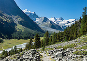 """The icy Bernina Range rises above Ova da Roseg river valley, near Pontresina, Switzerland, in the Bernina Alps, Europe. Tschierva Glacier flows from the peaks clustered on left: Piz Bernina (4049 m), Piz Scerscen (3971 m) and Piz Roseg (3937 m). At right (west), Roseg Glacier flows from Piz Glüschaint (3594 m). Val Roseg is in the Swiss canton of Graubünden (or Grisons / Grigioni / Grischun); the lower Roseg Valley is in Pontresina, whereas the upper valley is in an exclave of Samedan Municipality. Hike from Pontresina up Roseg Valley to Fuorcla Surlej for stunning views of Piz Bernina and Piz Roseg, finishing at Corvatsch Mittelstation Murtel cable car. Walking 14 km, we went up 1100 meters and down 150 m. Optionally shorten the hike to an easy 4 km via round trip lift. The Swiss valley of Engadine translates as the """"garden of the En (or Inn) River"""" (Engadin in German, Engiadina in Romansh, Engadina in Italian), and is part of the Danube basin."""