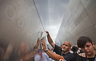 Glenn  Rosario makes a charcoal rubbing of the name of his lost brother while family members of those lost in the World Trade Center take a first walk through the Empty Sky Memorial 9/11 at Liberty State Park in New Jersey   on September 10th 2011  just before  the tenth anniversary of 9/11. They use<br />  charcoal and paper are provided by volunteers to  make rubbings of the name of their lost loved one. <br /> The memorial is two 30-Ft rectangular towers  208 feet by 10 inches long,  the width of the World Trade Center towers and with the names of the 746 New Jerseyans who perished after the terrorist attacks on 9/11, 2001  etched in stainless steel.
