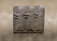 Photo of Hittite monumental relief sculpted orthostat stone panel of a Procession Basalt, Kargamis, Gaziantepe, 900 - 700 B.C. Anatolian Civilisations Museum, Ankara, Turkey.<br /> <br /> It is a depiction of three marching female figures in long dress with a high headdress at their head. These women are considered to be the nuns of the Goddess Kubaba. The figures in the front and behind have a bunch of spicy in their right hand while the figure in the middle has an empty right hand. Figures carry objects similar to a sceptre in their left hand.<br /> <br /> Against a brown art background. .<br />  <br /> If you prefer to buy from our ALAMY STOCK LIBRARY page at https://www.alamy.com/portfolio/paul-williams-funkystock/hittite-art-antiquities.html  - Type  Karkamıs in LOWER SEARCH WITHIN GALLERY box. Refine search by adding background colour, place, museum etc.<br /> <br /> Visit our HITTITE PHOTO COLLECTIONS for more photos to download or buy as wall art prints https://funkystock.photoshelter.com/gallery-collection/The-Hittites-Art-Artefacts-Antiquities-Historic-Sites-Pictures-Images-of/C0000NUBSMhSc3Oo