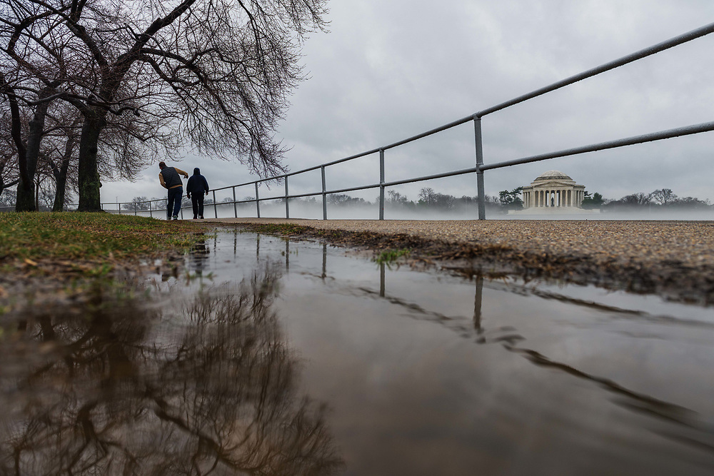 Two men walk along the Tidal Basin on an overcast day in Washington, D.C.