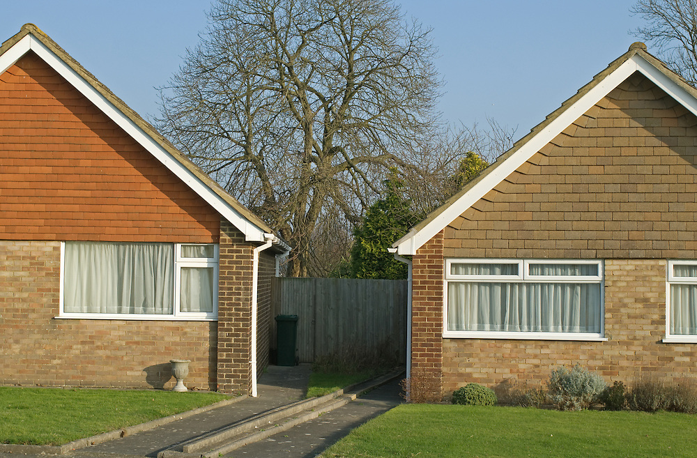 Two very similar detached suburban homes next door to each other.