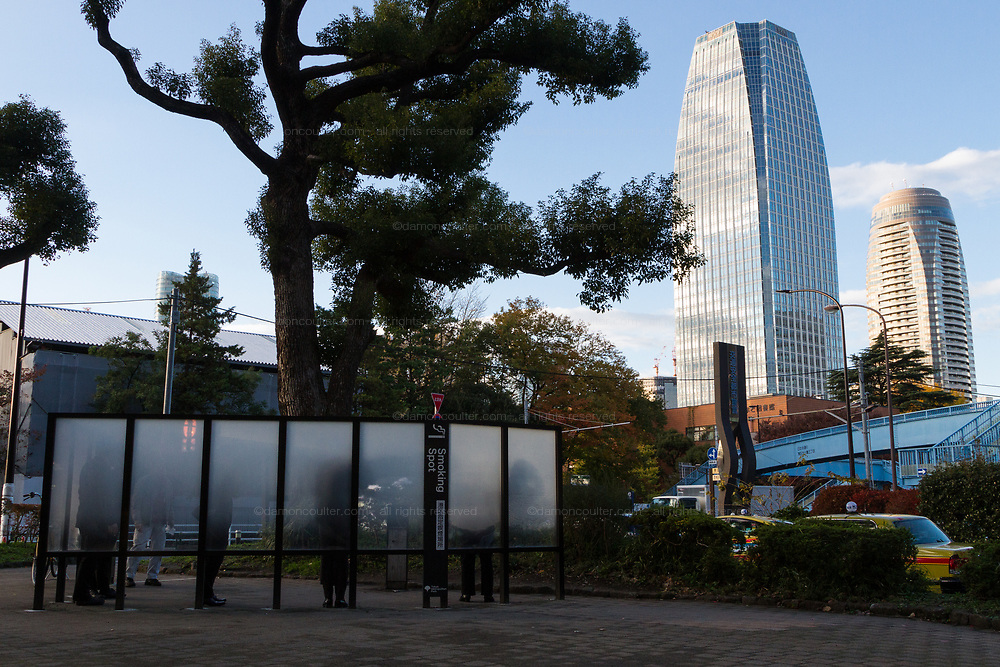 A smoking area in the street in front of some tall apartment buildings. Tokyo, Japan. Monday November 28th 2016