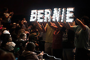 """Fans hold up """"Bernie"""" lights for the crowd before Bernie Sanders speaks at the Verizon Theater in Grand Prairie, Texas on April 19, 2017. (Cooper Neill for The Texas Tribune)"""