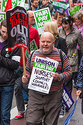 London, July 10th 2014. Plenty of cross-union support was on display as thousands of striking teachers, government workers and firefighters marched through London in protest against cuts and working conditions.