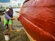 04 NOVEMBER 2015 - YANGON, MYANMAR: A worker repaints a small wooden ferry on the banks of the Yangon River in Dala. Dala is located on the southern bank of Yangon River across from downtown Yangon, Myanmar. Many Burmese live in Dala and surrounding communities and go across the river into central Yangon for work. Before World War 2, the Irrawaddy Flotilla Company had its main shipyards in Dala. That tradition lives on in the small repair businesses the work on the hundreds of small wooden boats that serve as commuter ferries for the people of Yangon. The boats are pulled up onto the riverbank in Dala and repaired by hand.    PHOTO BY JACK KURTZ