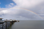 A rainbow showing the spectrum of colours is seen arcing across the sky above Llandudno pier, on 4th October 2021, in Llandudno, Gwynedd, Wales.
