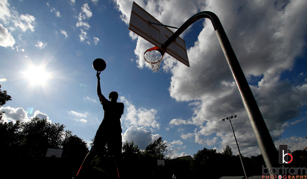 Marion Mills makes a late afternoon shot while playing basketball at Willow Street Park in New Britain, CT. (Photo by Kevin Bartram)