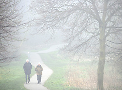 © Licensed to London News Pictures. 12/03/2016<br /> A couple walk through heavy fog in Foots Cray Meadows  in  Sidcup, Kent this morning. Photo credit: Grant Falvey