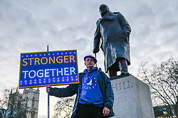 © Licensed to London News Pictures. 29/01/2020. LONDON, UK.  An anti-Brexit protester next to the statue of Winston Churchill in Parliament Square holds up an illuminated sign calling on holding the Boris Johnson, Prime Minister, and his government to account during the upcoming Brexit negotiations.  Britain will formerly leave the European Union at 11pm on 31 January.  Photo credit: Stephen Chung/LNP