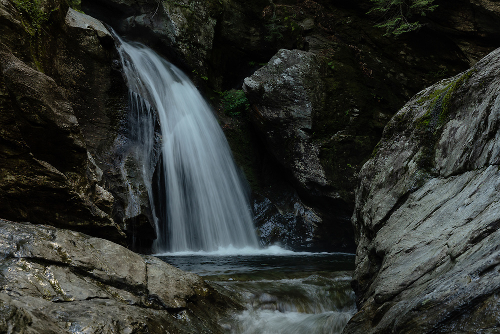 The powerful plunge at Bingham Falls on a warm summer afternoon in the forests of Stowe.