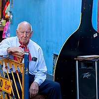 """An aged man sitting in front of a tango bar in """"La Boca""""."""