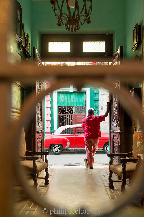 View for street San Cristobal Paladar with vintage car and man from behind bars, Havana, Cuba