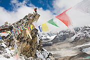 Jagged Globe mountain guide Alun Richardson takes pictures while standing on a rock spire covered with prayer flags below Kala Patthar overlooking the Changri Shar glacier, Khumbu region, Sagarmatha National Park, Himalaya Mountains, Nepal.