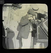 Magic lantern slide mother watching of two boys using a Roovers Metal Stamping Machine at the seaside, England, UK c 1900-1910