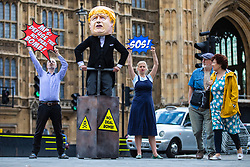 """© Licensed to London News Pictures. 03/09/2019. London, UK. Campaigners from Avaaz hold a photocall outside Parliament with a man dressed as Prime Minister Boris Johnson pushing the plunger on a """"No-Deal Bomb"""", as two pedestrians watch on. MPs return from recess today and may vote on legislation to block a no deal exit from the European Union. Photo credit: Rob Pinney/LNP"""