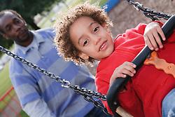 Man  pushing boy on a swing