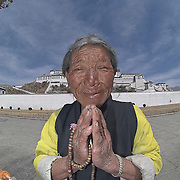 An elderly Tibetan woman prays below the Potala Palace, Lhasa, Tibet.