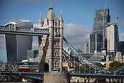 A red London bus crosses Tower Bridge with construction work in progress in the capitals financial district aka The Square Mile behind, on 5th October, 2017, in London, England.